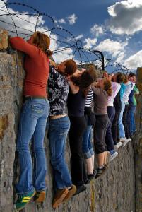 People Peering Over Wall